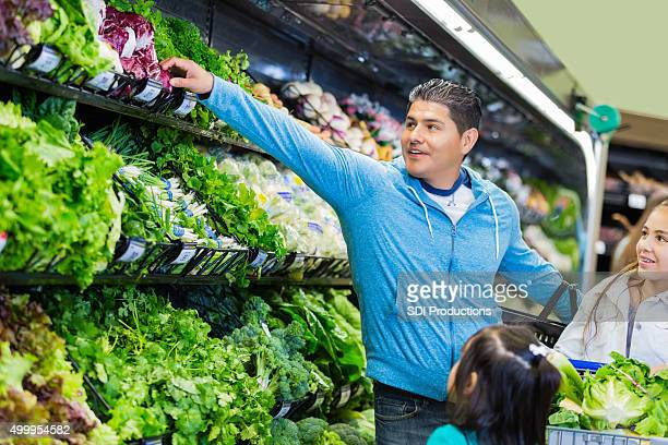 Hispanic father shopping for healthy food with young daughters