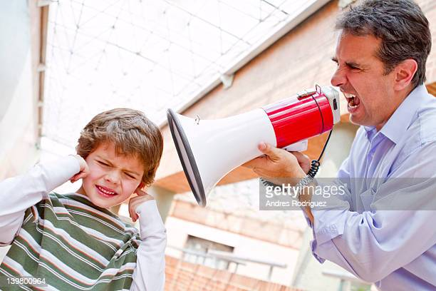 hispanic father shouting at son through bullhorn - fingers in ears stock pictures, royalty-free photos & images