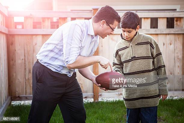Hispanic father teaching son to play football
