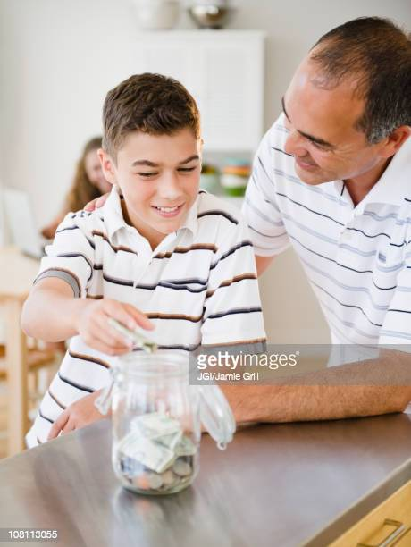 Hispanic father watching son put money into jar