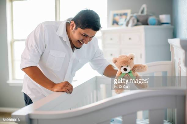 Hispanic father waving toy for baby in nursery