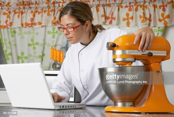 hispanic female baker typing on laptop - electric mixer stock pictures, royalty-free photos & images