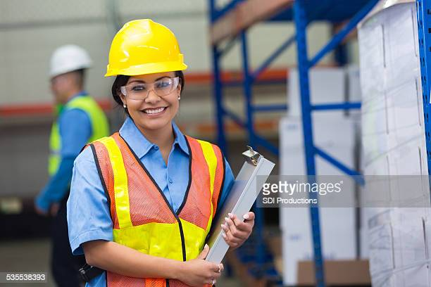 hispanic female blue collar worker in distribution warehouse - protective eyewear stock photos and pictures
