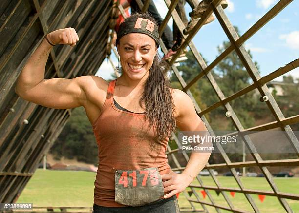 5K Hispanic female competitor flexing bicep.