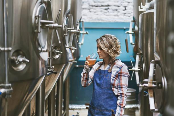 hispanic female craft brewer examining beer sample picture