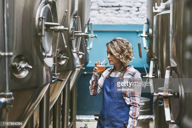 ビールサンプルを調べるヒスパニック女性クラフトビール醸造所 - 醸造所 ストックフォトと画像