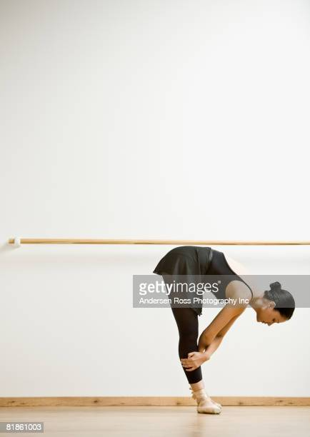 hispanic female dancer stretching - barre stock photos and pictures