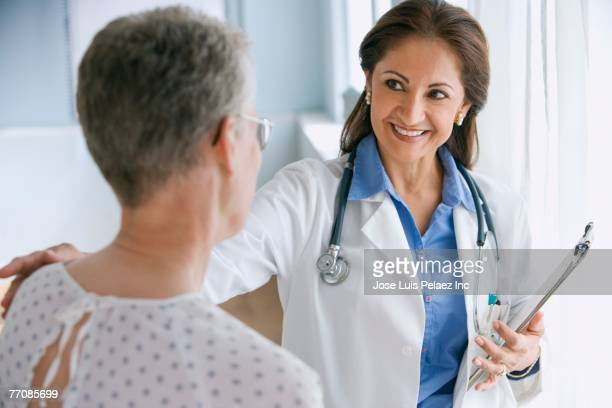 Hispanic female doctor smiling at patient