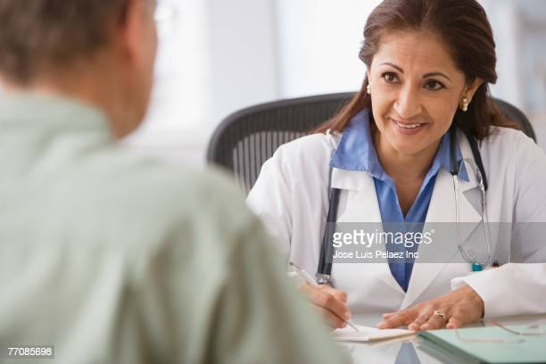 Hispanic female doctor talking to patient