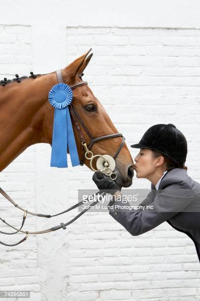 hispanic female equestrian kissing horse - riding hat stock pictures, royalty-free photos & images