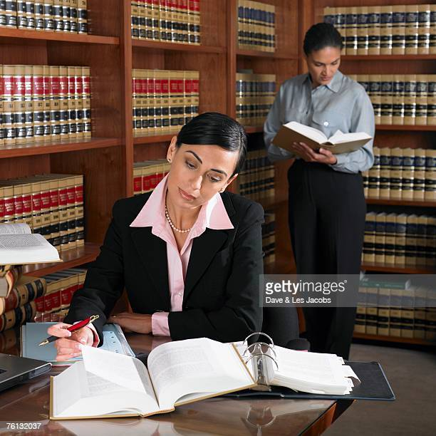 hispanic female lawyers working in office - lawsuit stock pictures, royalty-free photos & images