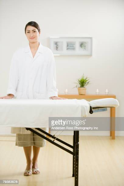 Hispanic female massage therapist next to massage table
