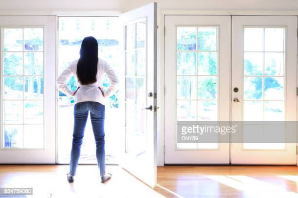 hispanic female millennial looks outside - french doors stock pictures, royalty-free photos & images