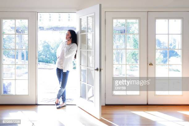 Hispanic Female Millennial Using Mobile Phone While Working At Home