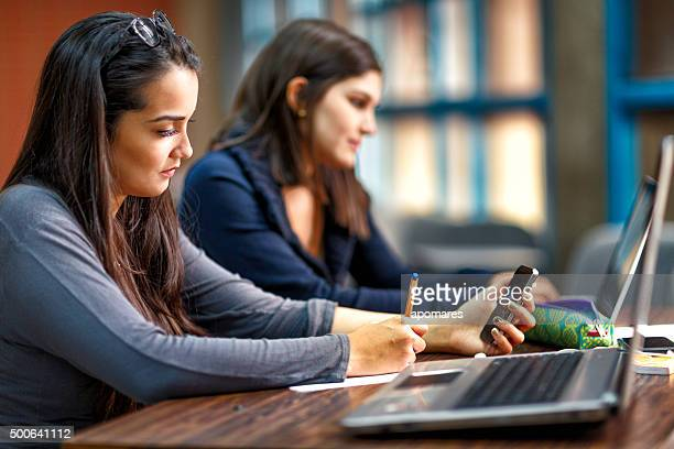 Hispanic female students studying and using laptop computer in classroom