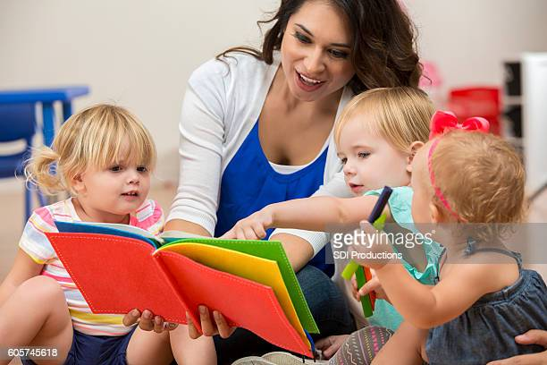 Hispanic female teacher reading a book to cute preschool students