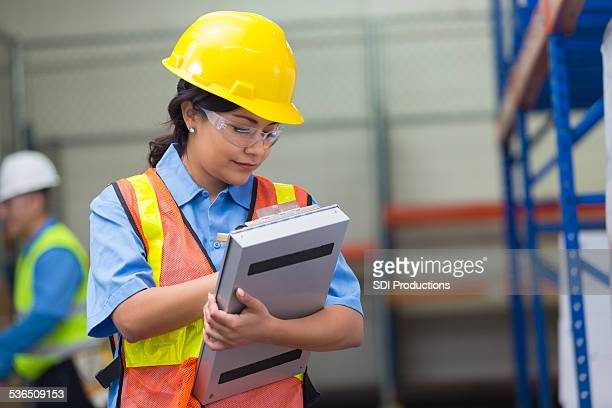 Hispanic female warehouse worker checking list on clipboard