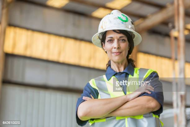 Hispanic female worker wearing hardhat and safety vest