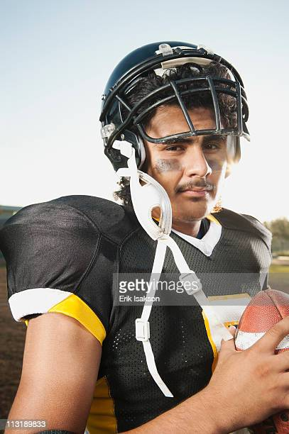 Hispanic football player holding football