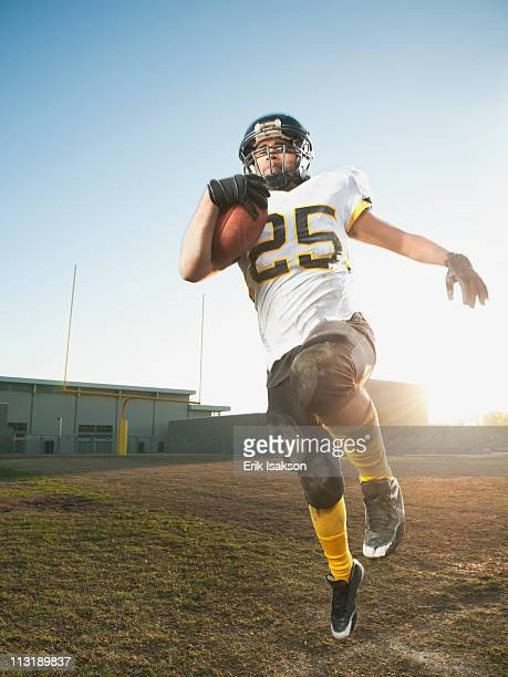 hispanic football player running with football - safety american football player stock pictures, royalty-free photos & images