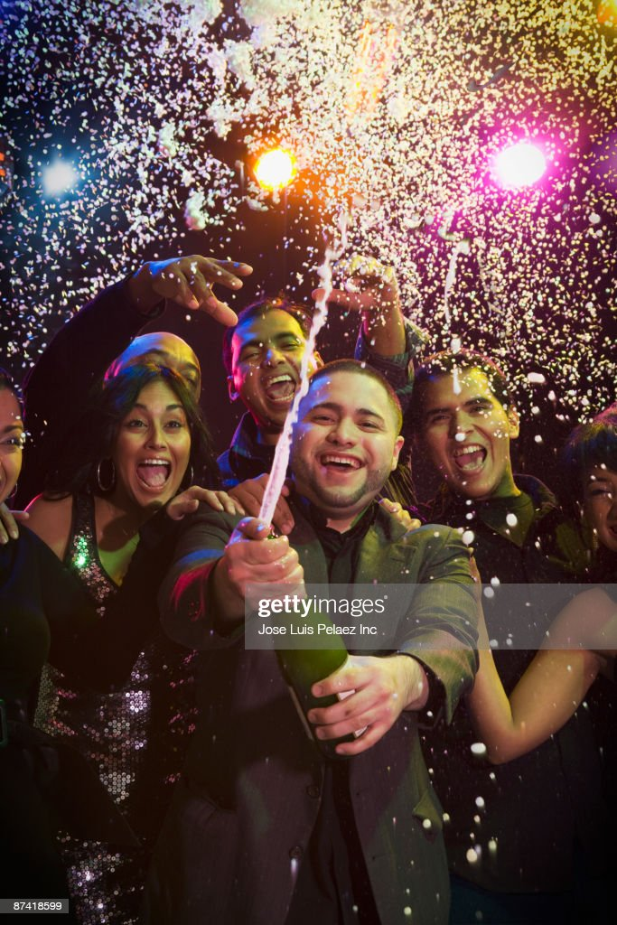 Hispanic friends drinking champagne in nightclub : Stock Photo