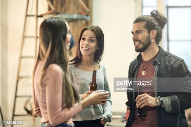 hispanic friends enjoying conversation at a social gathering - man bun stock pictures, royalty-free photos & images