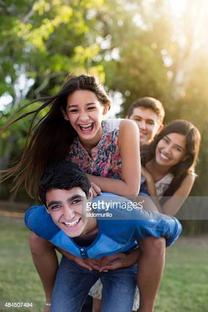 Hispanic friends enjoying piggyback