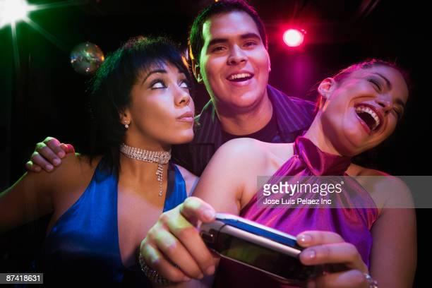 Hispanic friends in nightclub with camera phone