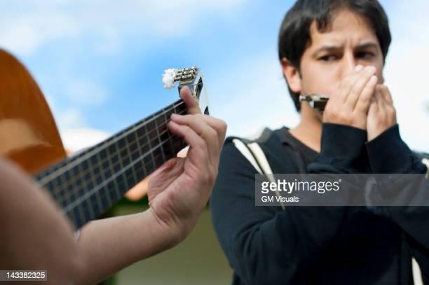 Hispanic friends playing guitar and harmonica