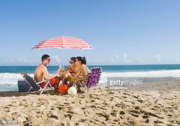 Hispanic friends relaxing at beach