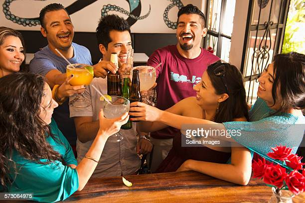 hispanic friends toasting with drinks at bar - mexican beer stock pictures, royalty-free photos & images