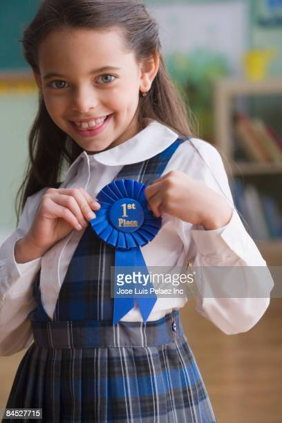 Hispanic girl adjusting 1st place ribbon