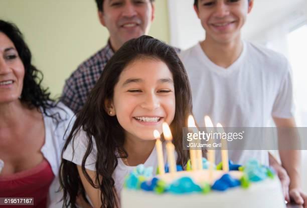 Hispanic girl admiring birthday cake