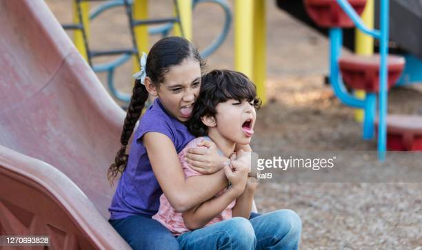 hispanic girl and brother on playground slide - teasing stock pictures, royalty-free photos & images