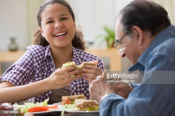 Hispanic girl and grandfather eating sandwiches