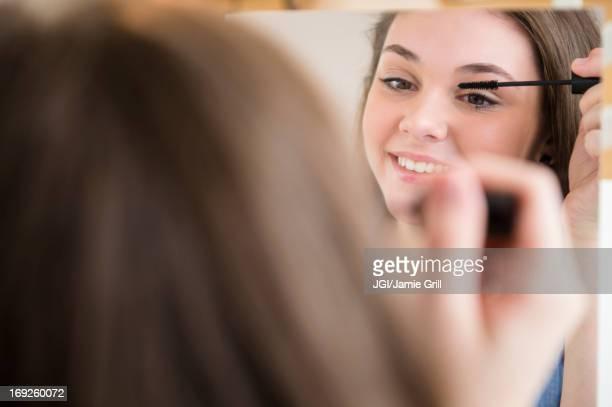 hispanic girl applying makeup in mirror - feminidade - fotografias e filmes do acervo