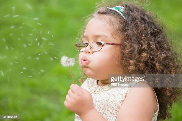 Hispanic girl blowing dandelion