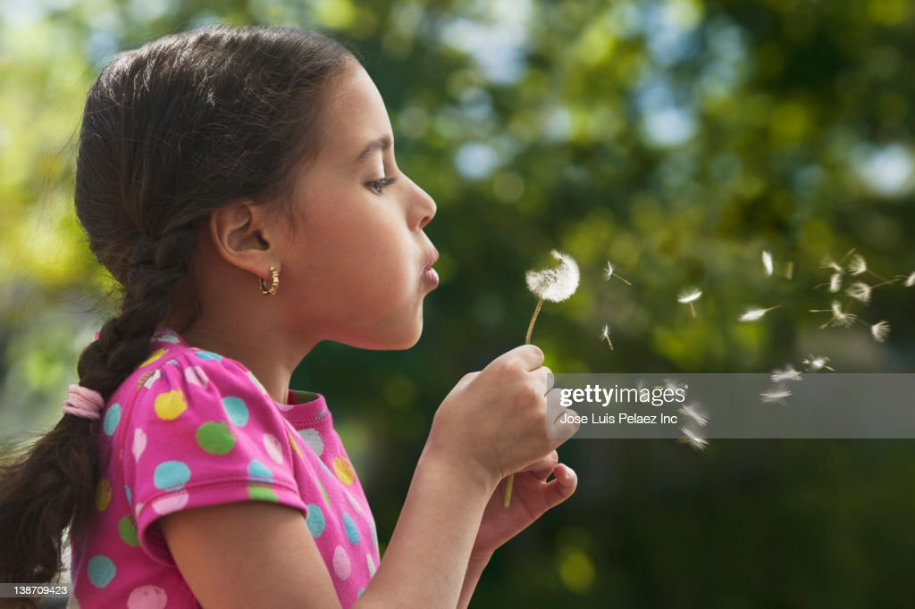 Hispanic girl blowing dandelion seeds : Stock Photo