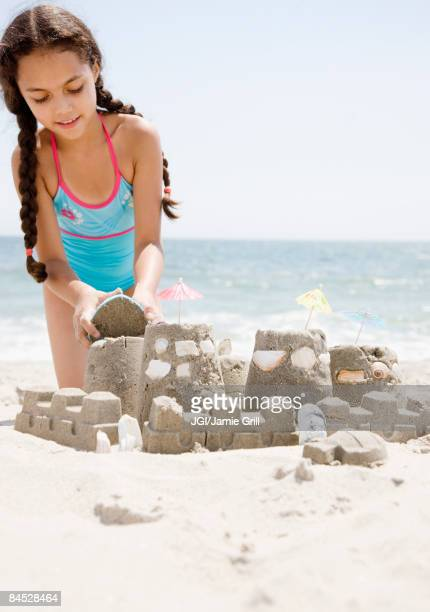 Hispanic girl building sand castle on beach