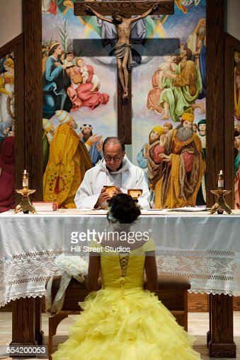 Hispanic girl celebrating quinceanera with priest in Catholic church