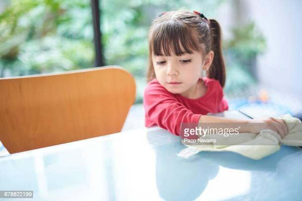 Hispanic girl cleaning table with towel