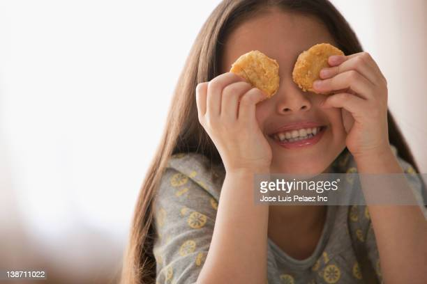 Hispanic girl covering eyes with chicken nuggets