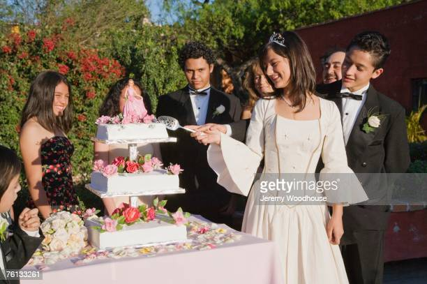Hispanic girl cutting cake at Quinceanera