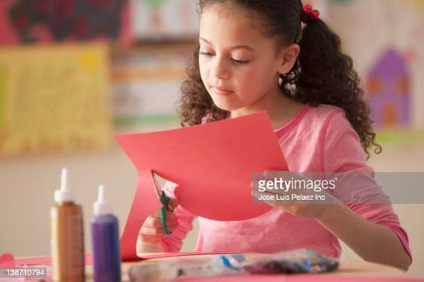 Hispanic girl cutting paper in classroom