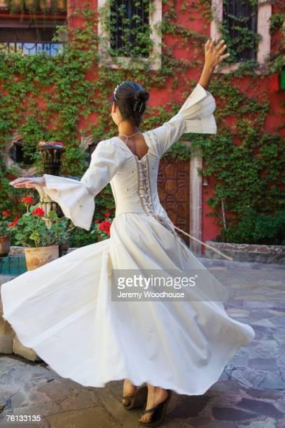 Hispanic girl dancing in Quinceanera dress