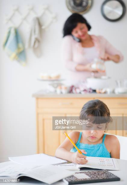 Hispanic girl doing homework with mother in background
