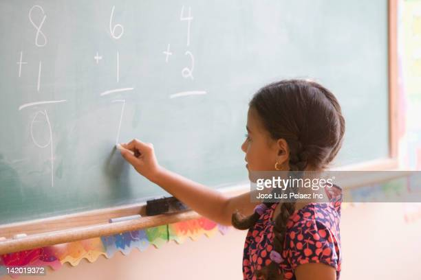 hispanic girl doing math on blackboard - mathematics stock pictures, royalty-free photos & images