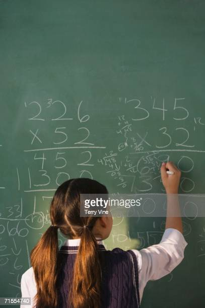 hispanic girl doing math on blackboard - fee stock pictures, royalty-free photos & images