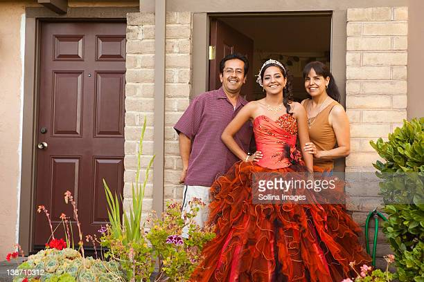 Hispanic girl dressed for quinceanera standing with parents