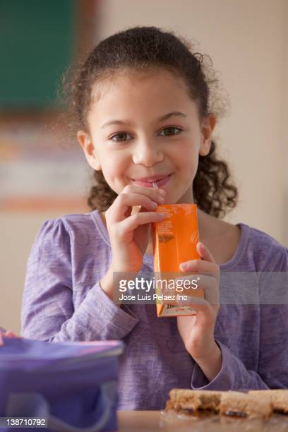 hispanic girl drinking juice box for lunch at school - juice carton stock photos and pictures